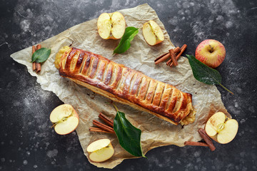 Freshly baked Apple and cinnamon strudel on baking paper