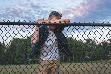 Sad teenager leaning against a chain link fence.