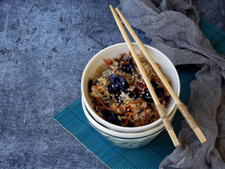 Rice with vegetables, carrots, purple cabbage, onion sprinkled sesame with chopsticks on grey background. Healthy vegetarian food. Space for text