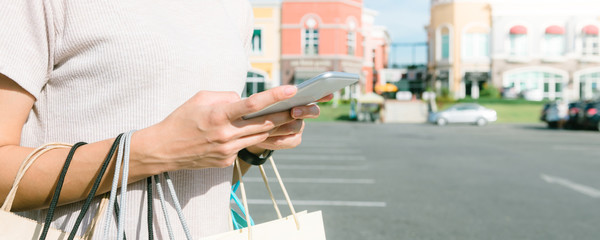 Young woman hold a shopping bags in her hand and chatting on her phone after shopping. Young Woman shopping in pastel town under the blue sky. Close up of outdoor shopping concept. Panoramic banner.