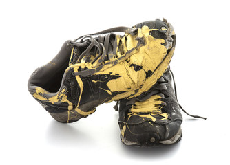 Pair of old paint covered training shoes on a white background