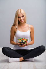 Woman with vegetarian salad, sitting on floor, on grey.