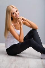 Woman in fitness wear, sitting on floor, against grey.