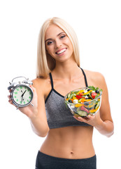 Woman in sportswear with salad and alarm clock