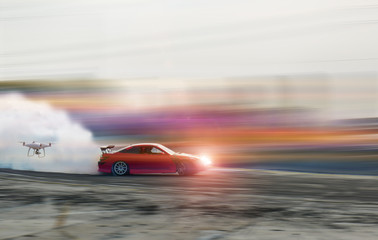 Blur of drifting car with flying drone to shoot picture and video car racing on speed track.
