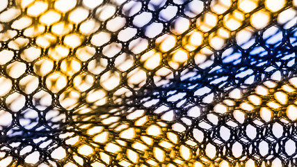 Abstract texture of net with hexagonal cells. Artistic detail of the decorative netting in black, yellow and blue color on white background. Concept of science, research, technology and industry.