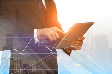 businessman with digital tablet and forex graphs