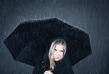 Junge Frau steht genervt unter Regenschirm im Regen