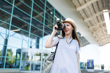 Young traveler tourist woman with backpack taking pictures on retro vintage photo camera at international airport. Female passenger traveling abroad to travel on weekends getaway. Air flight concept.