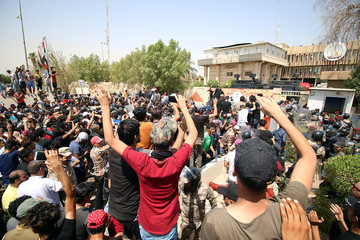 People gather during a protest near the main provincial government building in Basra