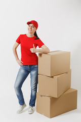 Full length portrait of delivery woman in red cap, t-shirt isolated on white background. Female courier or dealer standing near empty cardboard boxes. Receiving package. Copy space for advertisement.