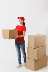 Full length portrait of delivery woman in red cap, t-shirt giving order boxes isolated on white background. Female courier near empty cardboard boxes. Receiving package. Copy space for advertisement.