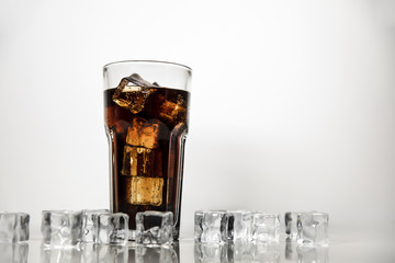 A refreshing drink of stake is poured into a glass beaker. Cola on white background with scattered ice cubes.