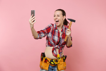 Overjoyed fun handyman woman in plaid shirt, denim shorts, kit tools belt full of instruments, hammer doing selfie on mobile phone isolated on pink background. Female in male work. Renovation concept.