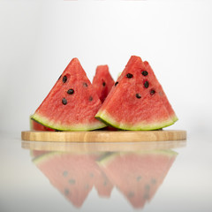 Berry watermelon in water splashes on a wooden tray. Reflection on table.