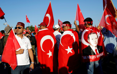 People hold Turkey's national flags and portraits of Turkish President Tayyip Erdogan as they arrive to attend a ceremony marking the second anniversary of the attempted coup at the Bosphorus Bridge in Istanbul