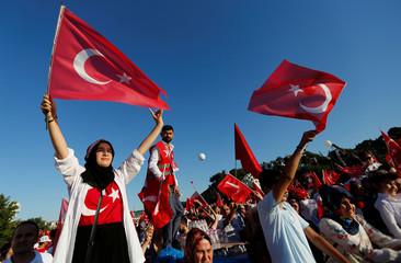 People wave Turkey's national flags as they arrive to attend a ceremony marking the second anniversary of the attempted coup at the Bosphorus Bridge in Istanbul