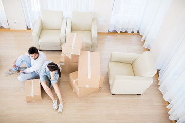 Young man and woman sitting on the floor while resting after relocation and carrying boxes