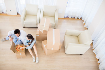 Over view of young couple siting on the floor, eating pizza and discussing where to put stuff from boxes