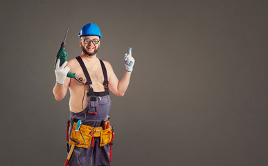 Fototapeta The fat funny man builder with a drill on a background for text. obraz