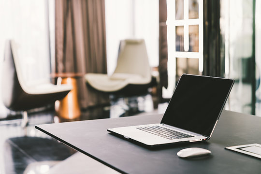 Laptop computer on work table in modern luxury contemporary office. Corporate business, internet information technology, or freelance job working at home concept