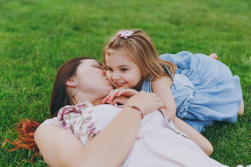 Happy woman in light dress kissing little cute child baby girl lie on green grass in park rest and have fun. Mother, little kid daughter. Mother's Day, love family, parenthood, childhood concept.