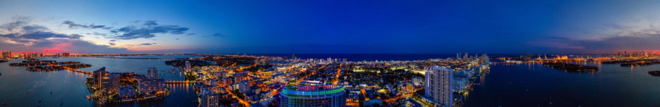 Aerial panorama Miami Beach twilight with neon city lights