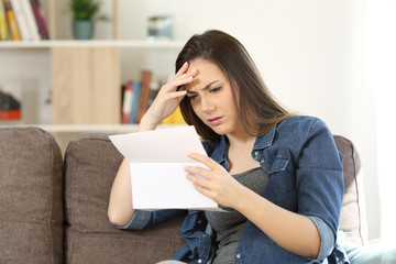 Concerned woman reading bad news in a letter