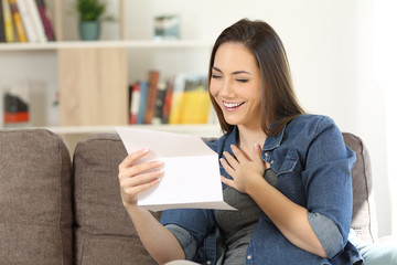 Candid woman reading hopeful news in a letter