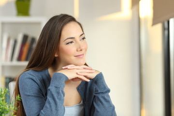 Confident pensive woman looking at side at home