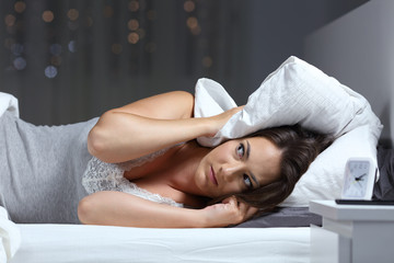 Desperate woman trying to sleep hearing neighbour noise