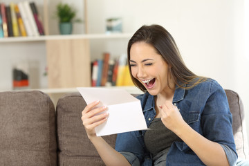 Excited woman reading great news in a letter