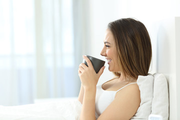 Girl drinking coffee at breakfast in the morning on the bed
