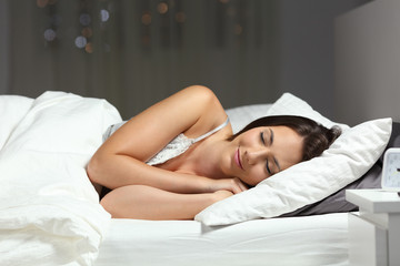 Happy woman sleeping on the bed in the night