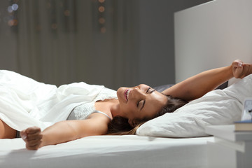 Happy woman stretching arms on a bed in the night