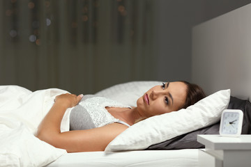 Insomniac woman unable to sleep on a bed in the night
