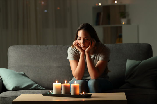 Distracted woman looking at candles light during blackout