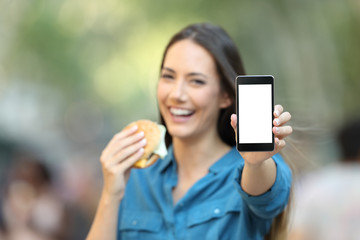 Woman holding a burger showing a phone screen