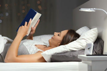 Woman reading a book in the night on the bed