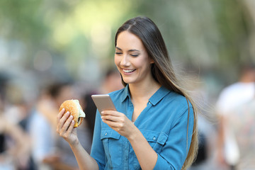 Woman holding a burger checking smart phone