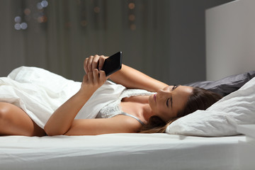 Woman using a smart phone in the night on the bed