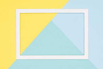 Abstract geometrical pastel blue, teal and yellow paper flat lay background. Minimalism, geometry and symmetry template with empty picture frame mock up.