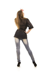 Girl with long hair, jeans, posing in the Studio.