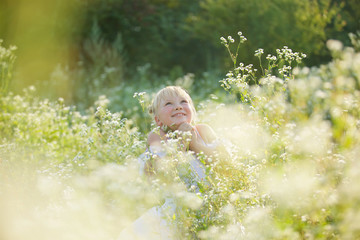 A blonde girl in a white ballet tutu stands among tall herbs and flowers.