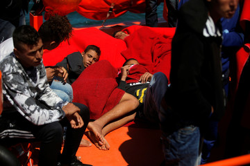 Migrants rest as they wait on a rescue boat to disembark after arriving at the port of Tarifa