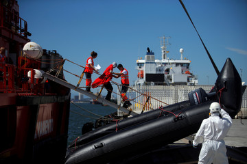 Migrant is helped by members of Spanish Red Cross at the port of Algeciras