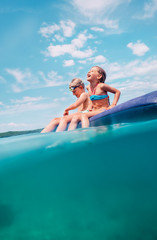 Over the deep blue sea: two childs have a fun when swim on inflatable mattress in the sea lagoon
