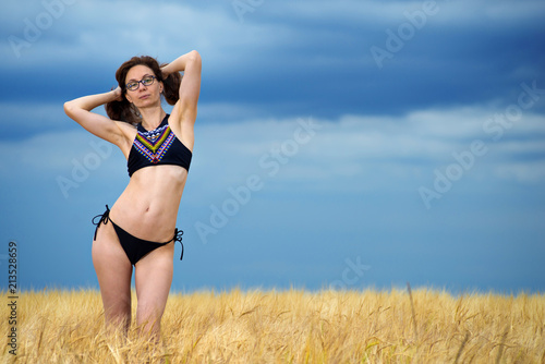 d4338d4a0e Sexy young woman in bikini in wheat field, free space.