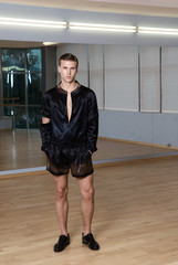 Man in elegant suite posing in fitness gym. High fashion young sexy man in black shorts and a black jacket