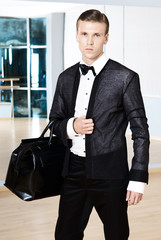 Male fashion, beauty concept. Elegant young fashion man holds in his hand a black bag and looking to the camera. Classic style. Studio shot